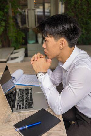 Foto vertical del empresario asiático pensando en el trabajo