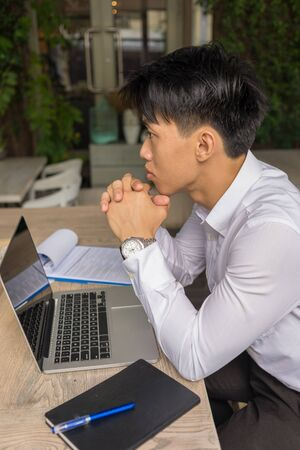 Vertical photo of Asian businessman thinking about work
