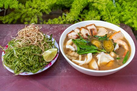 Vietnam traditional seafood and pork noodles soup and vegetables
