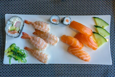 Fresh and delicious nigiri sushi on well-decorated square white plate Stockfoto
