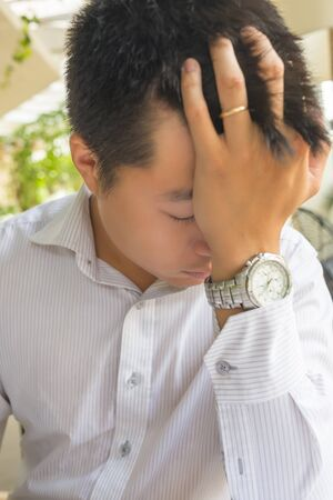 Frustrated Asian married man having headache and feel tired