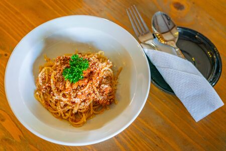 Plate of delicious spaghetti decorated with shredded cheese and parsley