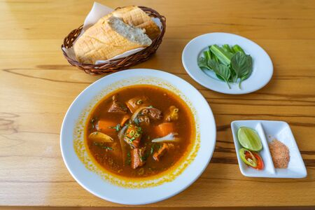 Bo kho- Vietnamese braised beef served with bread and vegetables