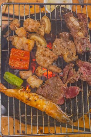 Vertical photo of meats and shrimp on charcoal grilling stove
