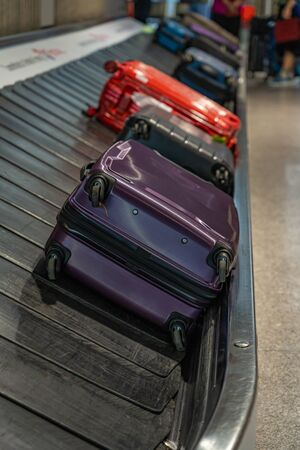Suitcases laying on luggage conveyor belt at airport waiting lounge