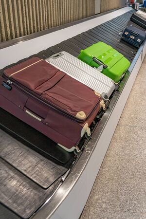 Suitcases laying on conveyor belt at baggage claim in airport Banque d'images