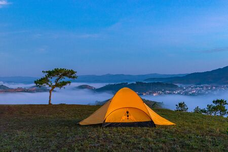 Yellow tent camping on hill under misty weather at dawn Stockfoto