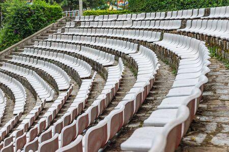 Empty white plastic seats at outdoor soccer stadium