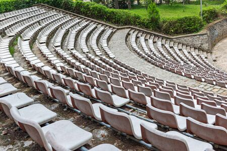 Rows of empty white plastic chair at outdoor stadium