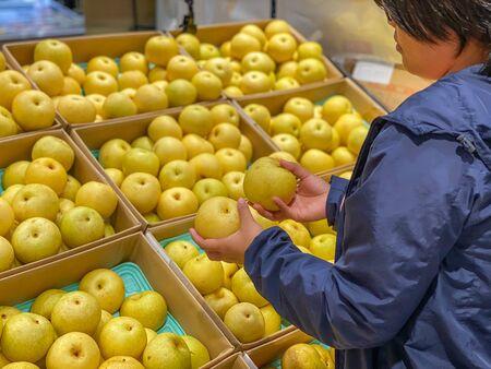 Asian woman choosing and buying yellowish pear at fruit store Reklamní fotografie
