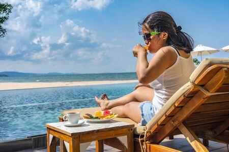 Femme asiatique buvant du jus d'orange au complexe de luxe Banque d'images
