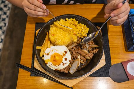 People eating sizzling beef sisig rice and fries on iron platter