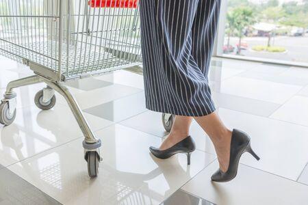 Close-up of woman foot wearing high heels while pushing shopping cart Stock Photo