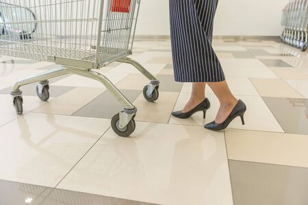 Office lady on high heels pushing shopping trolley in shopping mall