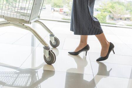 Woman on high heels pushing shopping trolley in shopping mall