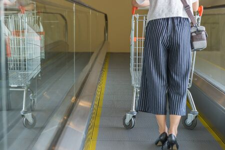 Woman on high heels using shopping trolley going up escalator Stock Photo