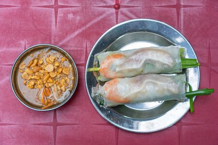 Delicious Vietnamese rice paper wrapped spring rolls and peanut sauce Stock Photo