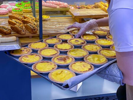 Salesperson putting fresh egg tarts onto showcase shelf in bakeshop