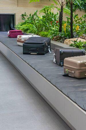 Suitcases on luggage conveyor belt at baggage claim waiting lounge Stock Photo