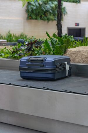 Blue suitcase on conveyor belt at arrival terminal in airport