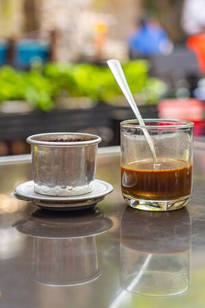 Vietnam styled brewed coffee and dripping filter on table