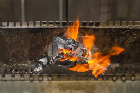 Flaming charcoal fire on barbecue grilling machine in kitchen