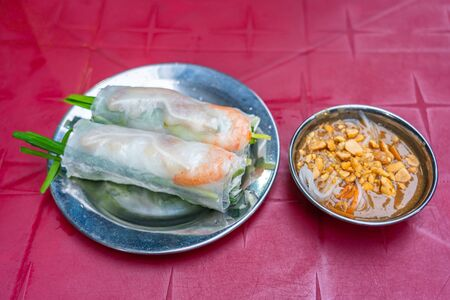 Vietnamese cuisine- fresh rice paper spring roll served with peanut sauce Stock Photo
