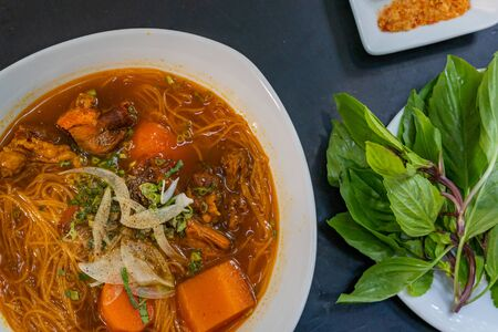 Delicious stewed beef brisket rice noodle served with basil
