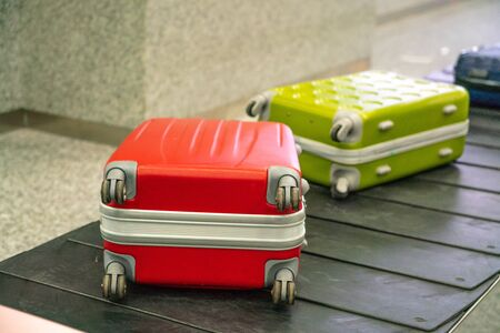 Red suitcase and green luggage on the conveyor belt in the international airport