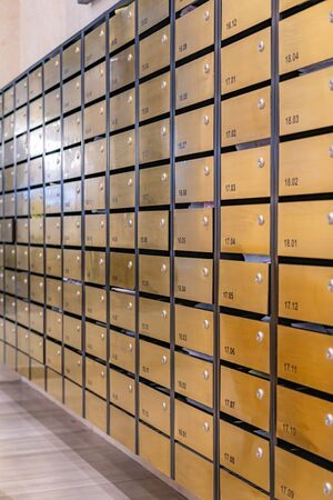 Rows of metallic mailbox in lobby of condominium building