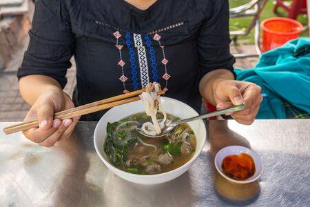 Young woman tourist Pho noodle soup - famous local food of Vietnam