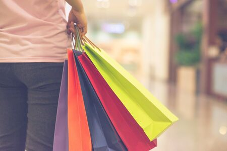 Close up photo of woman hand holding colorful shopping bags
