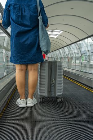 Traveler holding luggage and standing on automatic moving walkway Stock Photo