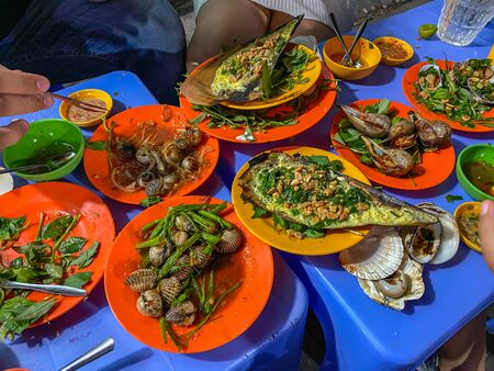 Delicious Vietnamese snails dishes on table at street food stall