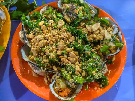 Vietnamese cuisine- delicious grilled cockles served with green onion oil and peanuts