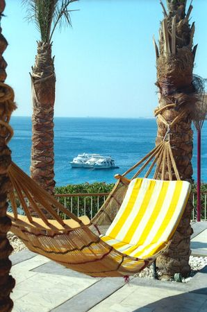 A hammock with the striped mattress is against the Sea and three cruisers