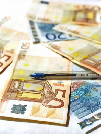 Banknotes of euro and a pen