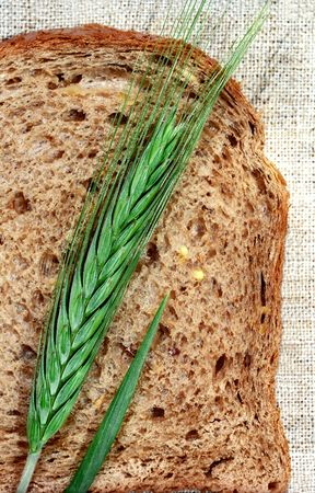 gramineous: Slice of bread and rye spica on canvas