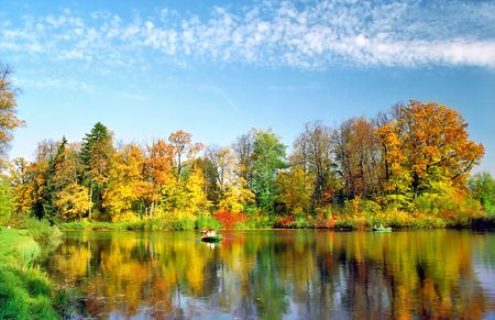 Lake with picturesque autumn trees and boats Stock Photo