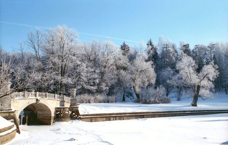 Winter river with old classical bridge in the park Stock Photo