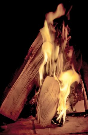 Firewood with flame in fireplace photo