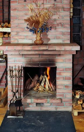 Village fireplace with fire irons and dead flowers on mantelshelf Stock Photo
