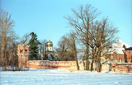 Red brick fortress wall and a church in winter