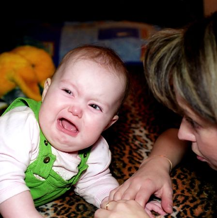 Crying baby and mother solacing her photo