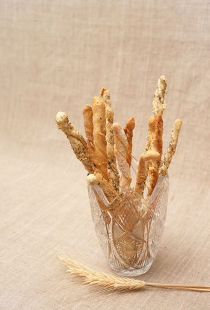 Breadsticks with seeds in vase and wheatear on canvas