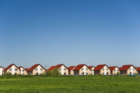 housebuilding: New cottages with red roofs and blue sky