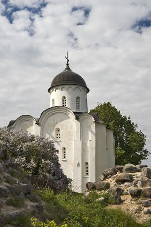 white  russian: White russian church with blossoming lilac and old fortress ruins