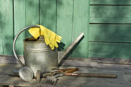 Garden tools with watering-pot and yellow rubber gloves