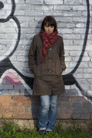 Girl penser � quelque chose sur le mur de graffiti