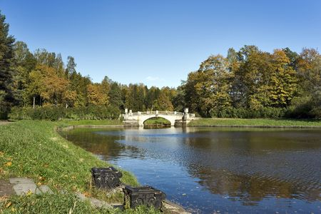 Classical bridge and an ancient pier in the autumn park